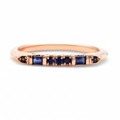 Marvelously moody sapphires of both baguette and round cuts dress up a band of 14-karat rose gold.