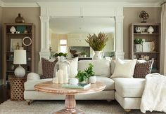 The Elegant Abode - living rooms - cafe au lait, walls, open, bookcases, mirrored, wall, off-white, linen, sofa, chaise lounge, Bamileke stool, table, round, pedestal, coffee table,