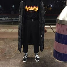 All black long coat, black graphic shirt, black FLOWY trousers, black vans