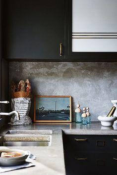Black kitchen with concrete worktop and splash back