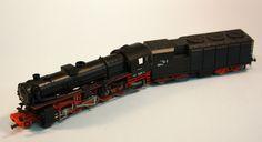 Locomotora de vapor amb tènder 150: Locomotora amb tènder de la DR rodatge tio 1-5-0, negra amb detalls vermells i inscripcions en blanc. Locomotora de vapor con ténder 150: Locomotora con ténder de la DR rodaje tipo 1-5-0, negra con detalles rojs y inscripciones en blanco.