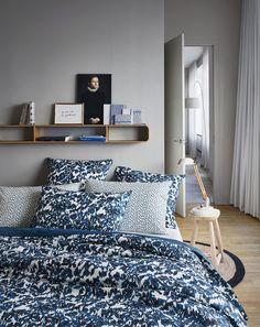 Dans une chambre grise un peu froide, association de tons bleus, de motifs chamarrés et de pois (parure de lit Mist, percale de coton, Paul & Joe by Madura).