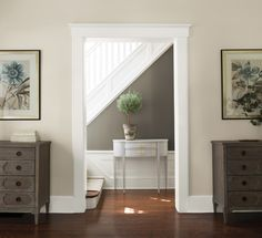 A gray hallway with white staircase and wainscoting includes a delicate console table and lustrous hardwood floors.
