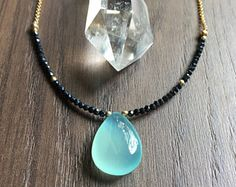 This luxe gemstone necklace features a flashy faceted rainbow moonstone and tiny round lapis lazuli gems. The moonstone is wire wrapped in 14k gold fill wire and the lapis lazuli beads are wire wrapped asymmetrically into the chain. Item Details:  ☆ Rainbow Moonstone has a faceted surface and measures 22x11mm ☆ Lapis Lazuli beads measure 3mm ☆ Chain is 14k gold filled rolo chain and measures 18-20 (includes a 2 extender)  Convo me with any questions!  See more of my work here…
