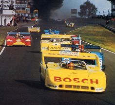 The cars on the first lap of a dramatic Interserie race in 1972. In the background the smoke of Herbert Müller's burning Ferrari 512 after it had exploded in the pitlane after a heavy crash. The swiss suffered only minor injuries (this time).