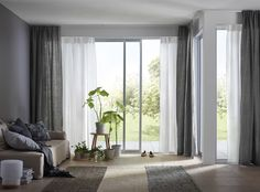 A bright living room featuring large sliding windows with two layers of white and beige sheer panel curtains that filters the daylight and one layer of dark grey thick curtains for privacy. Living Room Photos, Living Room Decor, Dark Grey Curtains, Purple Curtains, Floral Curtains, Colorful Curtains, Dining Room Windows, Layered Curtains, Double Curtains