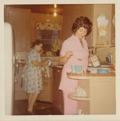 I like this one. Looks like the younger one has on a maternity outfit of the 50's and is making coffe or tea for the two of them and is putting that powdered cream inot the mugs. Check out all the vintage things in the kitchen. Real cool pic. <3