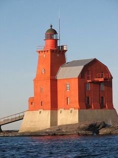 Porkkala Lighthouse located on a rocky shoal and marking a main shipping channel into Helsinkki, Finland. It was built in 1928 replacing a lightship station established in 1858. The square pyramidal tower is 69 feet tall and rises from one end of a two story keepers house.
