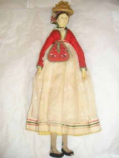 Doll, circa 1825-1835. Europe Jointed wood doll with painted features. Dressed in white chemise; laced and trimmed pique dress; red jacket; apron; stockings; shoes; straw hat over knitted red cap with tassel. Probably S. German or N. Italian.