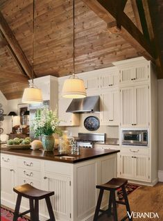 This rustic kitchen features a sloped wooden ceiling leading to beadboard cabinets and island with chopping-block top, all by Wood-Mode. - Veranda.com