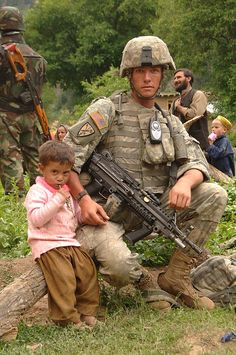 A little boy sits and holds the hand of U. Resolve Savage, from C Co. Arizona National Guard, during a medical capabilities program and humanitarian assistance supply hand out in the Nuristan province of Afghanistan June