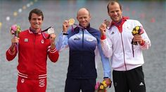 Eirik Veras Larsen of Norway celebrates on the podium with the gold medal, Adam Van Koeverden of Canada (L) the silver and Max Hoff of Germany (R) the bronze, following the men's Kayak Single (K1) 1000m Canoe Sprint finals on Day 12 of the London 2012 Olympic Games at Eton Dorney