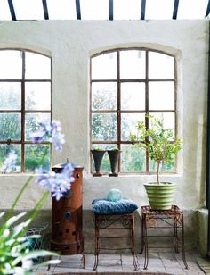 Love these industrial style windows in the thick set straw bale walls.