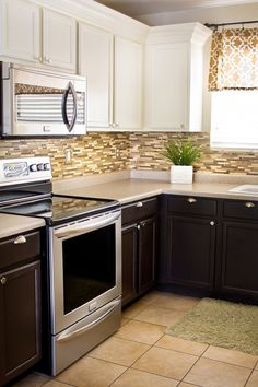 DIY Kitchen Updates on a Dime- dark lower cabinets, white upper cabinets, stainless appliances and hardware, glass tile backsplash. What I want my kitchen redo to look like.