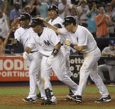 GAME 89: Monday, July 16, 2012 - New York Yankees' Raul Ibanez, second from left, is greeted by Robinson Cano, left, Alex Rodriguez, second from right, and Mark Teixeira after he hit a grand slam during the eighth inning of the baseball game against the Toronto Blue Jays at Yankee Stadium in New York. (AP Photo/Seth Wenig).
