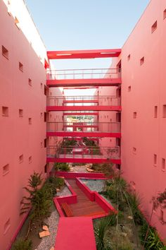 Pink walls frame rooftop garden of housing by Pietri Architectes
