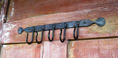 """Etsy seller Furnacebrook's Penny End Hook Rack. Vermont blacksmith shop hand forges  these penny end hook racks for keys, brooms, cooking spoons and untensils as well as pot holders. They are also very good at hanging coffee mugs.  Shown in our black oil finish but also available in our rust and gray forge finishes.  Aproximately 16"""" long with 5 of our small 1"""" hooks attached. These can be made in any length needed."""