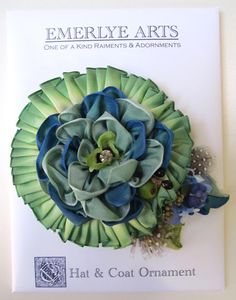 Two layers of green and blue ribbon, berries, flowers, feathers, and a vintage button make up this lovely ribbonwork adornment. Great look for a hat or coat. #millinery #judithm #hats