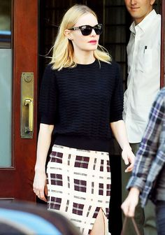 Kate Bosworth wears a black sweater, plaid skirt, and sunglasses by Coach