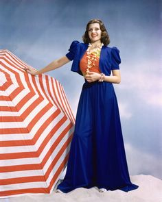 Rita Hayworth wearing a long blue skirt and a matching blue jacket with a red-and-yellow top with a shell necklace around her neck, posing beside an open red-and-white umbrella in a studio portrait, circa 1945.