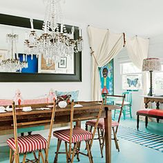 This Bohemian-chic dining room features striped bamboo chairs, a repurposed wood table, and fun turquoise floors.
