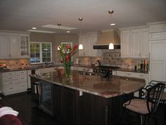 mix of dark and white cabinets, nice granite, simple pendants