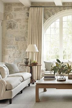 Interior design inspiration from a family room designed by Phoebe Howard with limestone wall, magnificent arched window, and white decor. - Interior design inspiration from a family room designed by Phoebe Howard with li. Living Room Remodel, Home Living Room, Living Room Designs, Living Room Decor, Living Spaces, Apartment Living, Stone Wall Living Room, French Living Rooms, Work Spaces