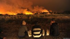 People watch a wild fire burning at the Ecological Reserve near Puerto Madero in Buenos Aires