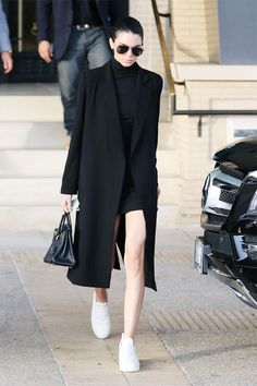 Kendall Jenner looks sleek in a black mini dress, long coat, white sneakers, and a Birkin bag