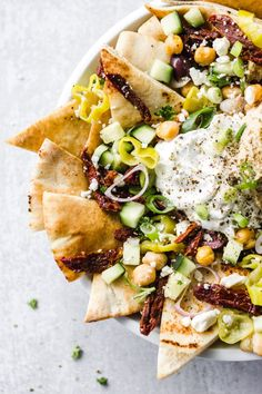 Make this easy and quick vegetarian appetizer that's loaded with crispy, warm pita pieces, Mediterranean toppings, and served with hummus and tzatziki sauce. | Fork in the Kitchen #recipe #superbowl #party #appetizer