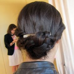 Simply Styled    Ted Gibson styled the Rachel Roy models' hair in a twisted, braided bun. He twisted both sides of the hair back, braided the hair into a bun, and finished the style off with a silver barrette.