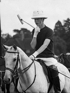 The Prince of Wales adjusting his chinstrap as he goes out to play for Rangers, in a match for the Chairman's Cup against Chiesmans during a Household Brigade Polo Club match, at Windsor Great Park
