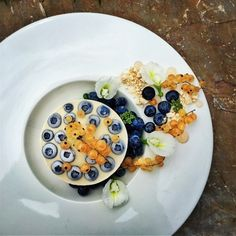 Raw coconut cake with avocado & cacao layers, meringue soil, fresh blueberries and white currants.