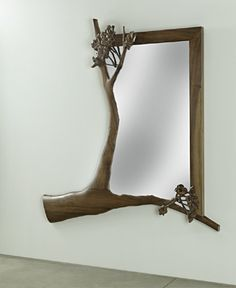 Richly-figured claro walnut framed mirror is boldly and sumptuously hand-carved to suggest a transformation of what we view. People and place aren't simply reflected, they're seen, through the pattern of the tree's branches. Limited series production.