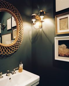dramatic powder room, black or very dark walls, gold, white Wicker mirror in a dark, striking powder room Dark Green Bathrooms, Grey Bathrooms, Small Bathroom, Bathroom Colors, Bathroom Green, Dark Gray Bathroom, Natural Bathroom, Gold Mirror Bathroom, Bathroom Photos