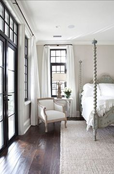 .I love the neutral tones of this bedroom w/ the wood floor and painted black trim around the windows. stunning