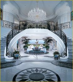 An amazing entryway, tiled in marble, looks through to the backyard a double staircase is the main focal point, with a fancy wrought iron railing (via beautiful staircases - Bing Pictures)