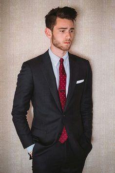 Slim suit w nice red tie.