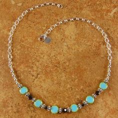 """A beautiful nature inspired necklace featuring stunning blue green Picasso coin shaped stones and smoky topaz crystals. A smooth and sparkling necklace accented with Bali beads and sterling silver chain - a sophisticated fashion accessory!    Necklace measures approximately 18"""" in length.    Custom orders are welcome at Makana Jewelry Designs!"""