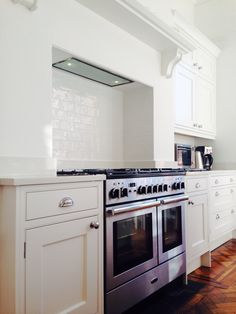 White kitchen, in frame cabinets, stainless steel range cooker and door furniture, parquet floor