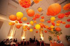 Des pompons en papier de soie +/- des lanternes chinoises à différentes hauteurs…  http://www.jolismariages.com/2011/09/05/le-potentiel-glamour-dune-salle-des-fetes/