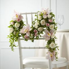 This is smart from interflora for your chair backs http://blog.interflora.co.uk/wp-content/uploads/2012/12/Wedding-Chair-Decoration.jpg
