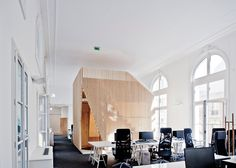 Boxy timber meeting spaces with seating, lockers and a slide.