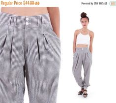 These adorable and versatile 1990s high waist pants feature a grey and white mini checkered print, front pleats and a baggy fit that gradually tapers