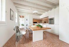 La zona giorno della casa in Veneto realizzata da Didone Comacchio: cucina su misura in total white e tavolo in tinta. Le sedute sono Dsw Eames Chair di Vitra in versione bianca; i pavimenti originali sono alla veneziana