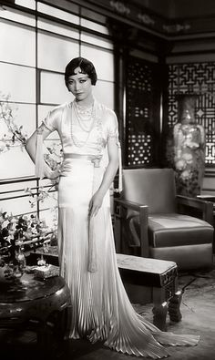 Anna May Wong in glamorous, white satin gown with embroidery detail on bodice, sash at waist and pleated skirt