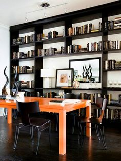 A masculine home office with a bright orange desk and a full wall of shelving provides an organized place to work with a few eclectic touches, such as the kudu horn centerpiece.