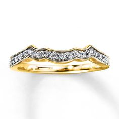 A row of round diamonds decorates this lovely wedding band for her. The ring has a total diamond weight of 1/5 carat and is set in beautiful 14K yellow gold. Diamond Total Carat Weight may range from .18 - .22 carats.