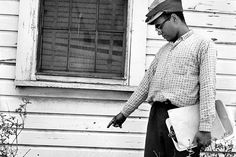 Robert P. Moses, field secretary of the Student Nonviolent Coordinating Committee, pointing out holes left by the shotgun blast in the wall of a home across the street from the voting drive headquarters in Greenwood, Miss.