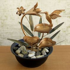 hummingbird fountain features copper-metal blooms and metal leaves that have a green patina. Water flows from the large metal flower to each petal and down into the black plastic bowl. - See more at: http://www.bitsandpieces.com/product/hummingbird_fountain/gifts#sthash.JZRa6waF.dpuf